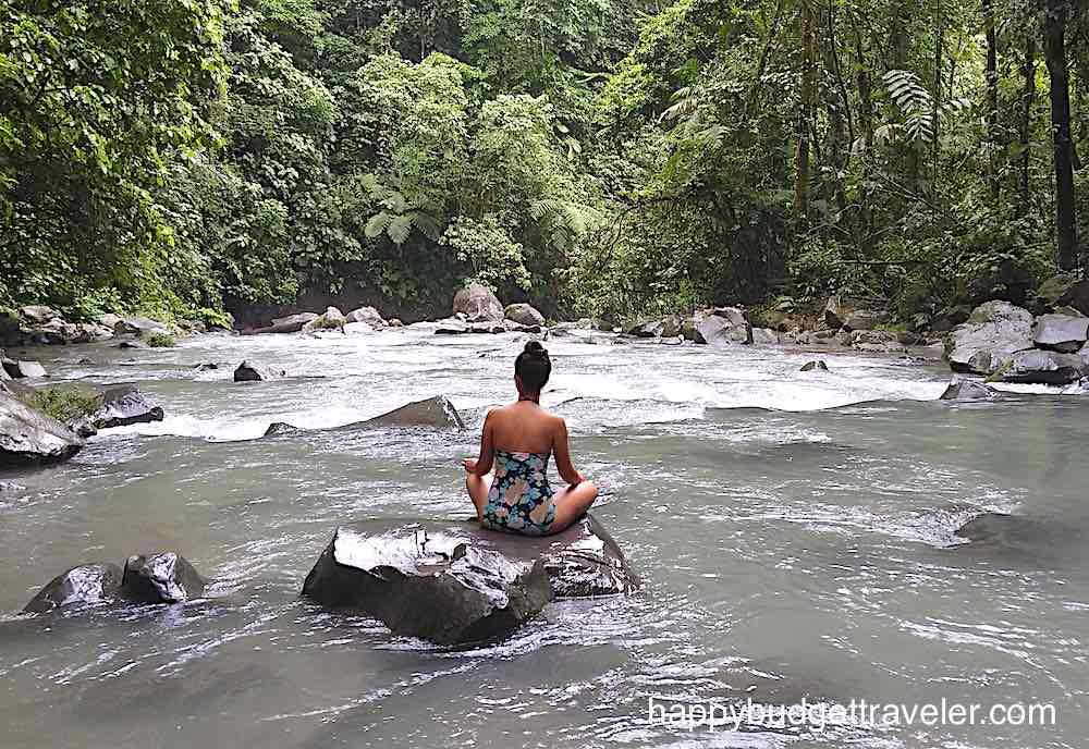 girl meditating on rock at La Fortuna waterfall